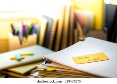 Make Copy; Stack of Documents. Working or Studying at messy desk.