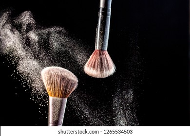 Make up cosmetic brushes with powder blush explosion on black background. Skin care or fashion concept.