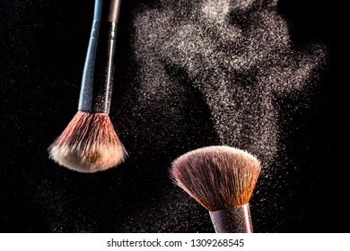 Make up cosmetic brushes with powder blush explosion on black background. Skin care or fashion concept