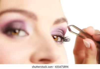 Make up and cosmetics. Woman plucking eyebrows depilating with tweezers. Attractive girl tweezing eyebrows