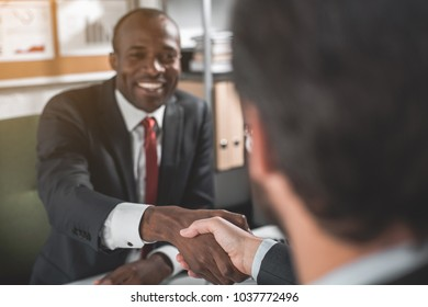 Make deal. Portrait of happy young successful african businessman is wearing official clothes and sitting opposite at table with his partner. He is smiling while shaking hands