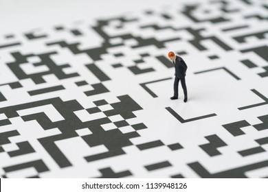 Make a decision for solution for business idea concept, miniature figure businessman standing at the center of confusing QR code labyrinth maze thinking to find the way out.