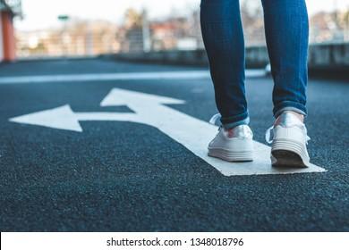 Make decision which way to go. Walking on directional sign on asphalt road. Female legs wearing jeans and white sneakers.