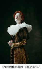 I make decisions. Medieval redhead young woman in golden vintage clothing as a duchess standing crossing hands on dark green background. Concept of comparison of eras, modernity and renaissance.