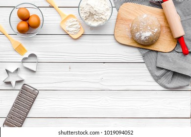 Make dough. Ingedients flour, eggs near cookware on white wooden background top view copy space