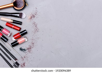 Make up the essentials. A set of professional makeup brushes and cosmetics on a gray, concrete background. Space for your text or logo. Perfect for a beauty blog. Flatly, horizontal.