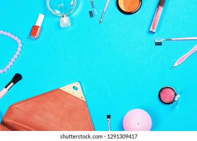 Make up and fashion woman essentials: cosmetics, make-up accessories, candle, perfume, necklace, nail polish and bag of trendy in 2019 coral color on blue background. Flat lay style with copy space.