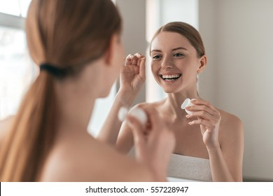 Make it a habit. Over the shoulder view of young beautiful woman holding dental floss and smiling while looking in the mirror