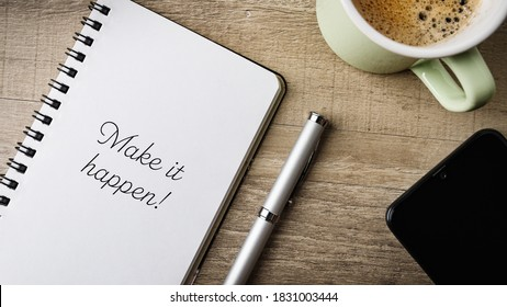 Make it happen! Flat lay. Work area with notepad, pen, cell phone and a cup of coffee.
