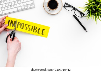 Make the impossible possible. Cutting the part im of written word impossible by sciccors. Office desk. White background top view space for text