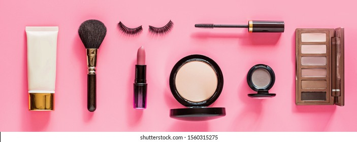 Make up items on pink color background. Horizontal web banner. Set of luxury decorative cosmetics flat lay, top view, mockup, template. Minimal style. Beauty blogger concept.