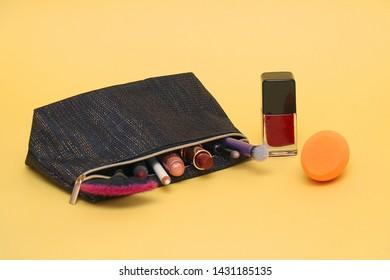 Make up lipsticks, eyeshadows and brushes inside cosmetic case on yellow background