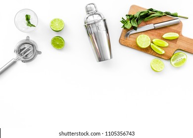 Make mojito cocktail with lime and mint. Shaker, strainer, glass near slices of lime on cutting board on white background top view copy space