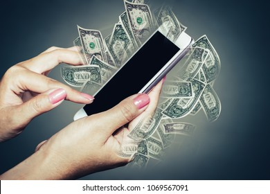 make money online concept, woman hand using technology mobile phone with banknotes in background