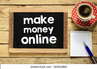Make money online on blackboard. Make money online On blackboard with cup of coffee, notebook and pen on wooden background