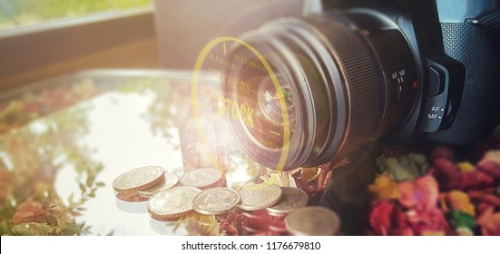 "make money with stock photos concept, camera lie on the colorful table with coins in front of the camera lens, add an effect of circle line and ""stock photos"" text on it"