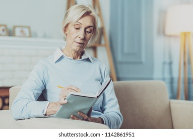 Make notes. Attentive female looking downwards while writing notices