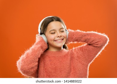 Make outside noise quieter and music sound better. Little girl relaxing with melodious sound. Cute kid listening to sound track in headphones. Small child enjoy electronic sound playing in earphones.