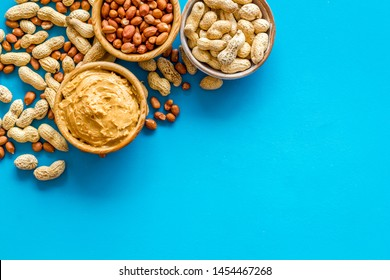Make peanut butter with nuts and paste in bowl on blue background top view copyspace