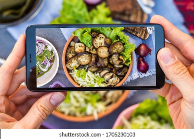 Make phone picture of food. Smartphone photography of vegan food. Eggplants. Creating blogger content. Woman hands. Overhead.