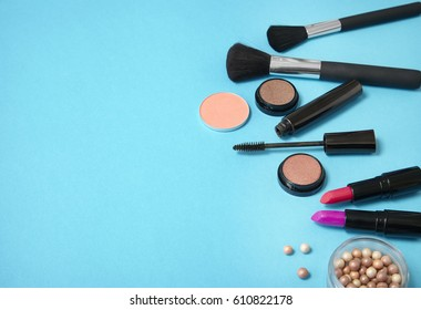 Make up products arranged on a bright blue background, with empty space at side