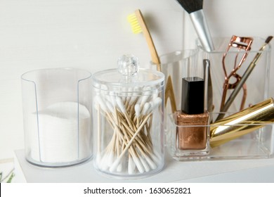 Make up products organizing concept. Beauty products in organizer container box on tidy way on minimalist shelf. Cotton pads stacked, Q-tips and make up brushes.