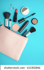 Make up products spilling out of a pale pink cosmetics bag on to a bright blue background