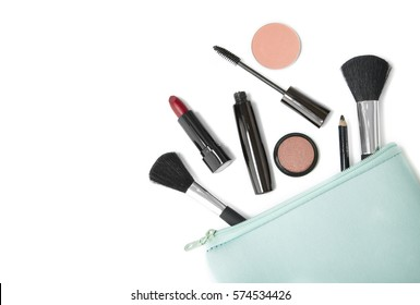 Make up products spilling out of a pastel blue cosmetics bag, isolated on a white background and blank space at side