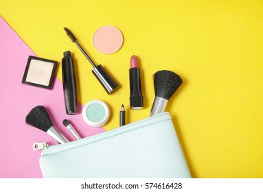 Make up products spilling out of a pastel blue cosmetics bag, on to a bright yellow and pink background with empty space at side