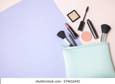 Make up products spilling out of a pastel blue cosmetics bag, on a pink and purple background with empty space at side