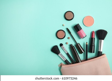 Make up products spilling out of a pastel pink cosmetics bag on to a turquoise background, with empty space at side