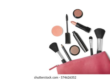 Make up products spilling out of a pink leather cosmetics bag, isolated on a white background with blank space at side
