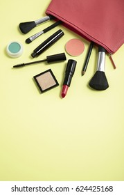 Make up products spilling out of a pink leather cosmetics bag on to a pastel yellow background, with blank space below