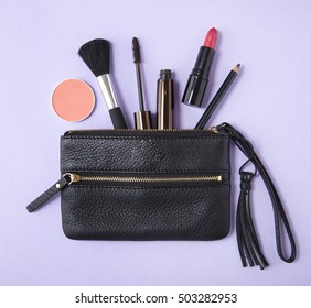 Make up products spilling out of a small leather clutch purse on to a pastel purple background