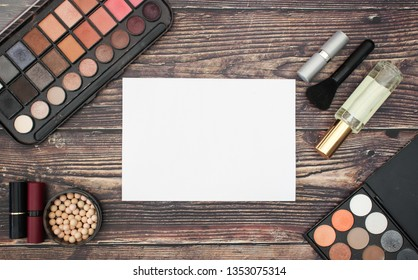 Make up products and white paper on wooden table