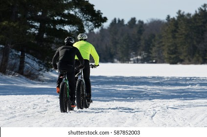 Make riders winter cycling on fat bikes on a frozen lake in winter