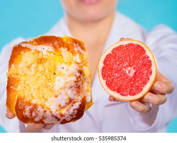 Make the right dietary choice concept. Nutritionist comparing diets options, holding cake sweet food and grapefruit on blue