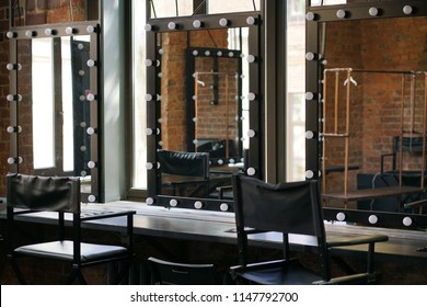 make up room with mirrors and lamp bulbs