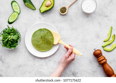 Make spinach pancakes. Hand flips pancake with a spatula. Grey background with spinach leaves, avocado, cucumber and spices top view copy space