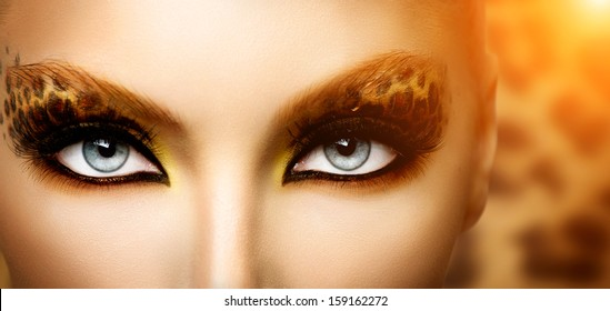 Make up. Beauty Fashion Model Girl with Holiday Leopard Makeup. Golden Wild Cat Eyes Make-up Eyeshadow. Beautiful Woman Face with Perfect skin. Animal Make up