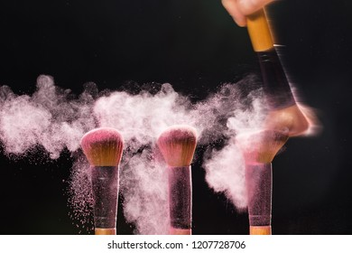 Make up, beauty and mineral cosmetic concept - Cosmetics brush and explosion light pink colorful makeup powder over black background