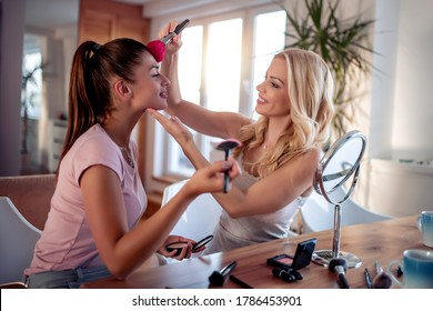 Make up, friendship and leisure concept,two smiling  girls applying make up at home.