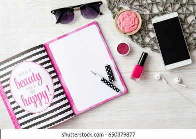 Make up, sunglasses, note, phone and headphones on white wooden table