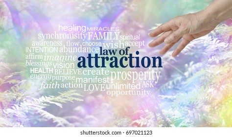 Make use of the Law of Attraction Word Cloud - female hand reaching towards a LAW OF ATTRACTION word cloud  on a multi colored wispy fantasy style woodland trees and fern background