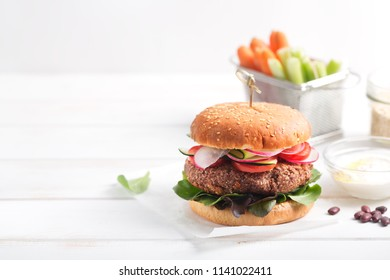 To make a vegetarian burger, combine the cooked beans and kinoa in a blender and make a cutlet. Stir a roll and put a cutlet and a lot of fresh vegetables. Add natural Greek yogurt