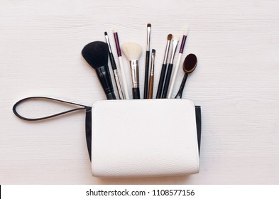 Make up or visage background. Female bag and different make up accessories, brushes, lipstick, and pencils.