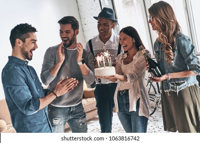 Make a wish! Happy young man celebrating birthday among friends while standing in room with confetti on the floor