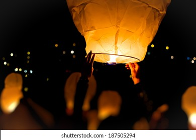Make A Wish.Yellow lantern in human hands on dark background
