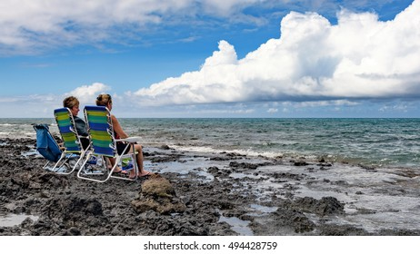 Makena, United States - August 7, 2016: Two middle aged women, sitting on folding chairs, enjoy the view of La Perouse Bay from the lava fields of Makena on Maui island, Hawaii