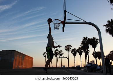 Makes a dunk. Boy playing in Venice Beach in a game of a street basketball. California.